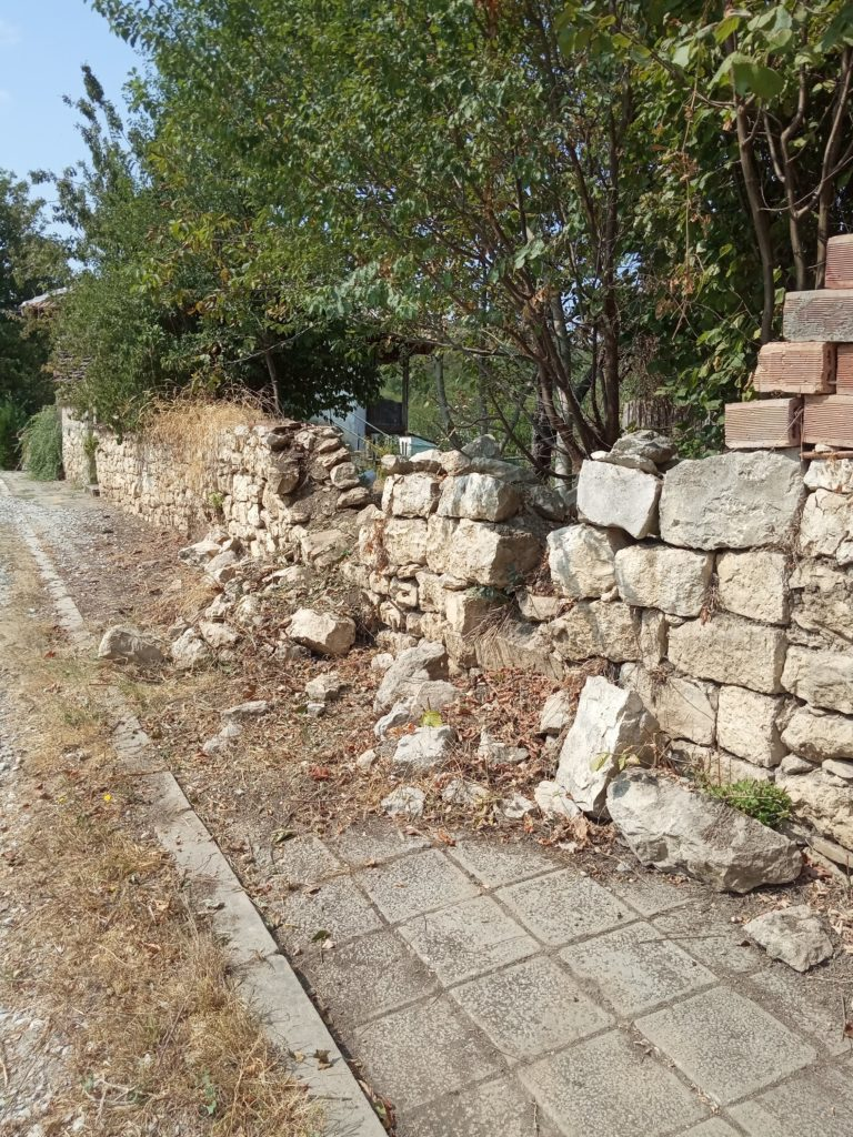 The damaged stone wall that needed repair